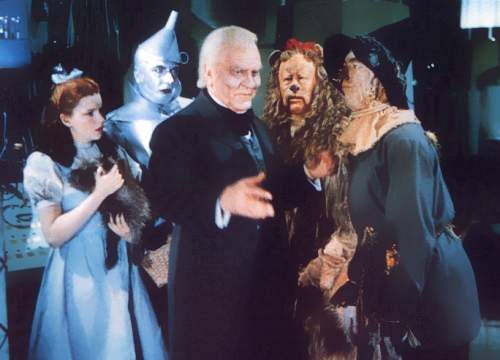 Dorothy, the Tin Woodman, the Cowardly Lion, and the Scarecrow surround the Wizard of Oz
